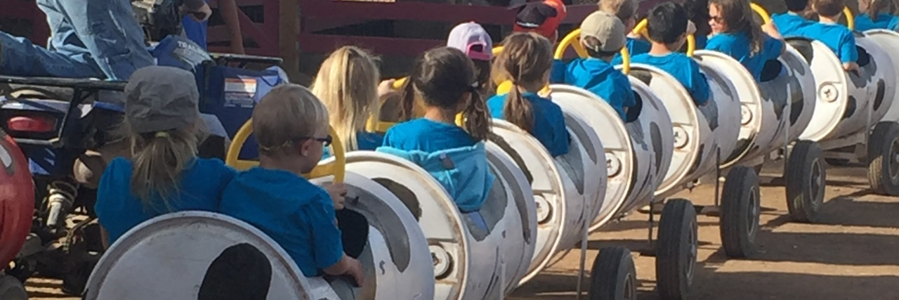 Children wearing blue shorts riding a single car train at school event or fair. Back view, no faces visible.