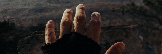 point of view shot of hand outstretched to barren landscape