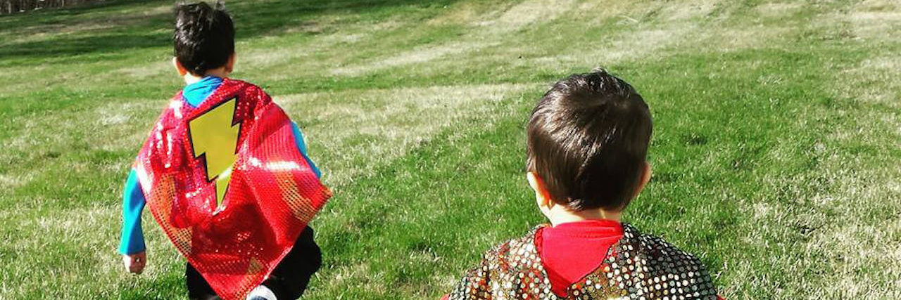 neena's two sons running in the grass with superhero capes