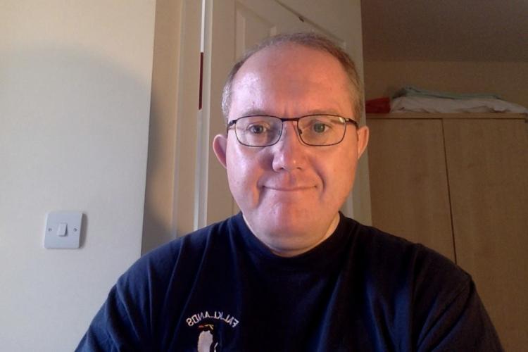 Neil smiling, wearing glasses