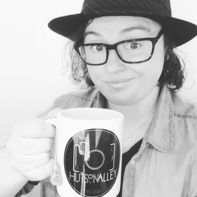 sally holding a mug, looking into the camera