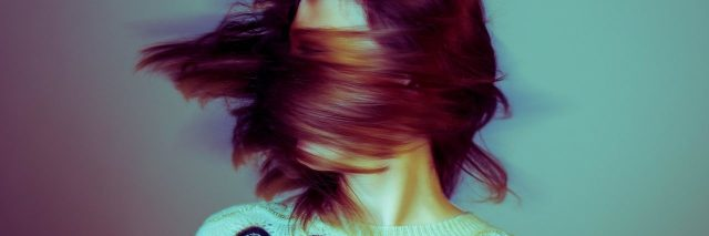 high contrast color blurred image of woman swinging hair covering face