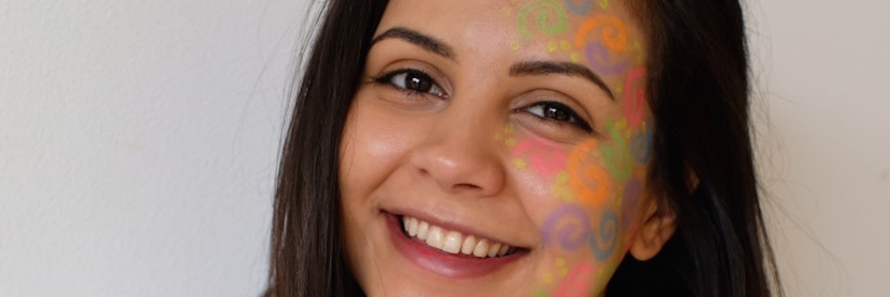 """the author with """"rare"""" colors painted on her face for rare disease day"""