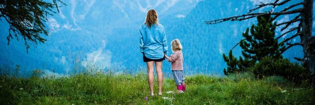 Mother and daughter standing together in clearing in front of mountains