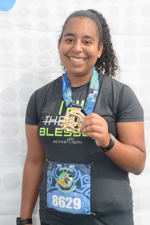 woman smiling and holding a medal around her neck after running a marathon