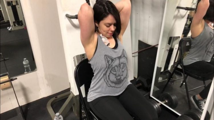 woman in a gray tank top and an IV in her chest lifting weights in the gym