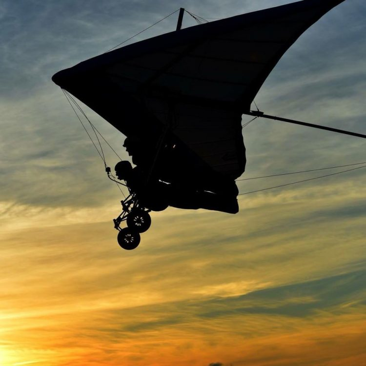 silhouette of a person flying against the sunset
