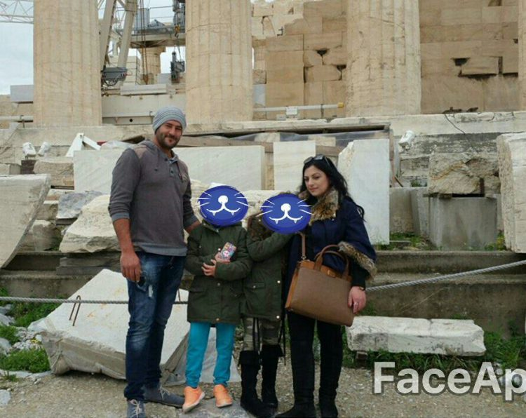 woman with her husband and two kids in front of the Acropolis in Greece