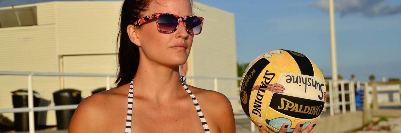 woman wearing a bikini and holding a volleyball on a sand court