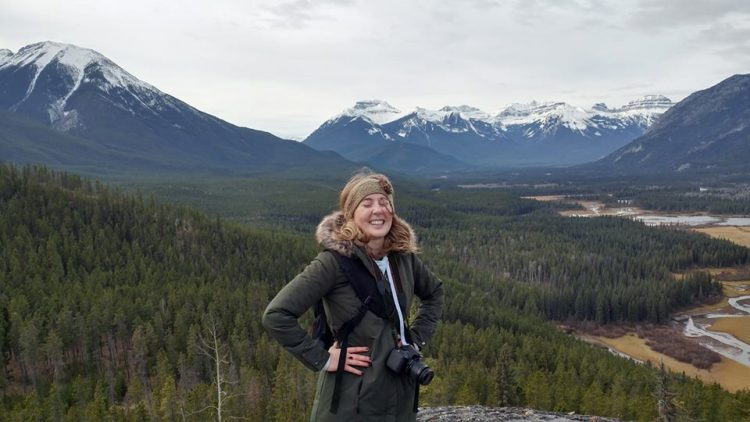 woman wearing a puffy jacket with a camera around her neck smiling with her hands on her hips at the summit of a mountain overlooking a mountain range and forest in alberta