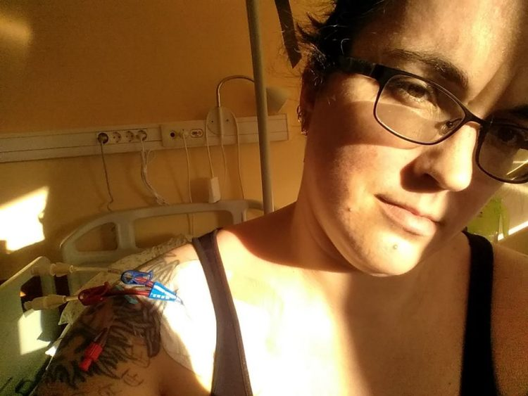 woman taking a selfie in the hospital with sunlight hitting her face and chest