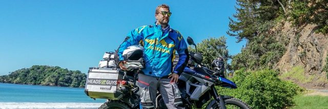 Colby Ellis posing in front of motorcycle while circumnavigating the world for mental health awareness with HeadsUpGuys