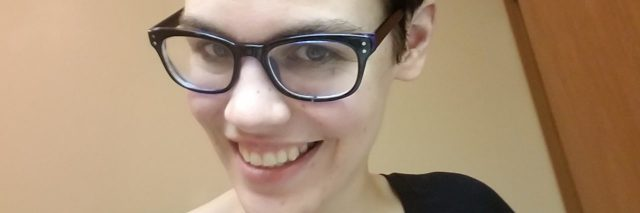 selfie of the author. she is smiling and wearing a black shirt and glasses.