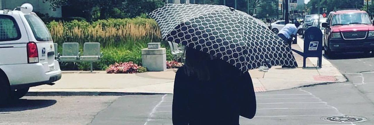 A picture of the writer walking down the street with an umbrella and in long sleeves.