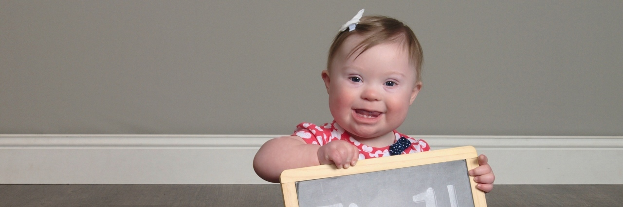 """Little girl with Down syndrome sitting on floor and holding a sign that reads, """"I'm 1!"""""""