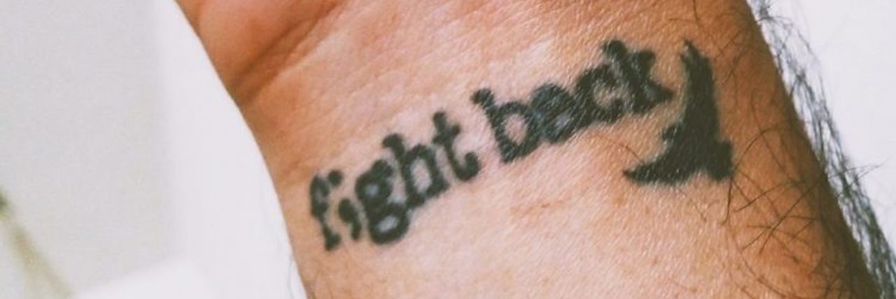 "Tattoo on a wrist that reads ""Fight back"""