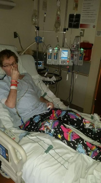 man in a hospital bed covering his nasal tube with his hand and wearing pajama pants with rainbow-colored kittens on them