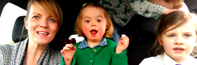 Screen shot of little girl with Down syndrome in car with mom and two siblings singing
