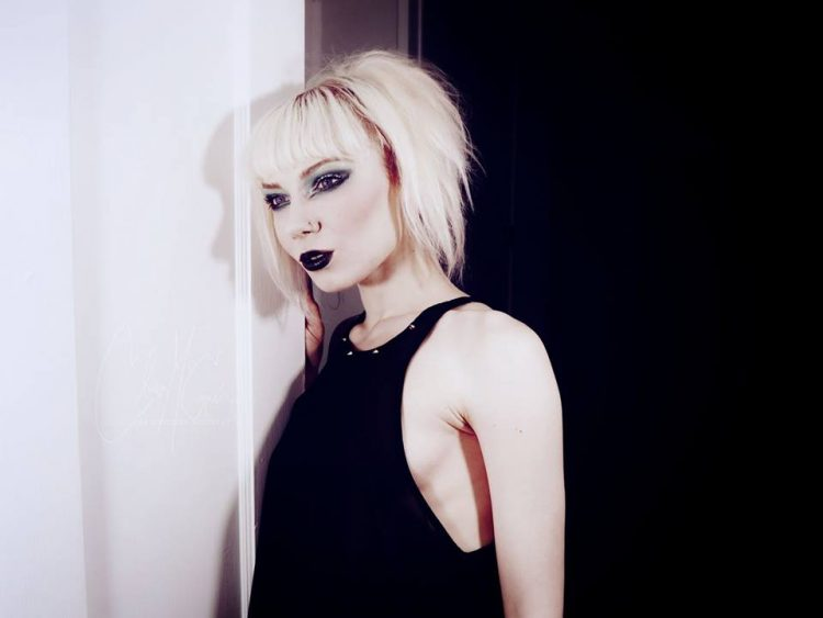 photo of a woman with blonde hair wearing a black shirt and purple lipstick and leaning against the wall in a pose
