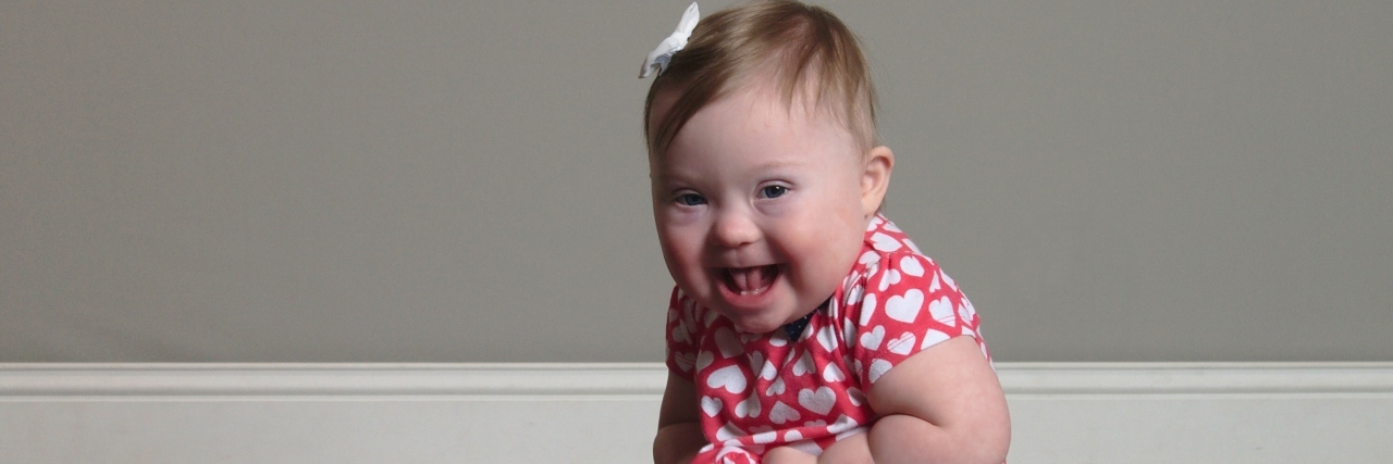 Baby girl with Down syndrome sitting on floor smiling at camera