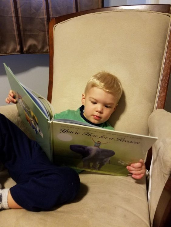 young boy sitting in an armchair holding a book