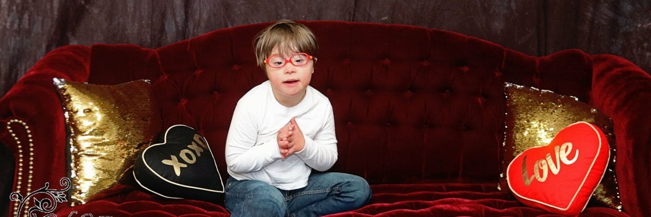 Boy with Down syndrome sitting on couch