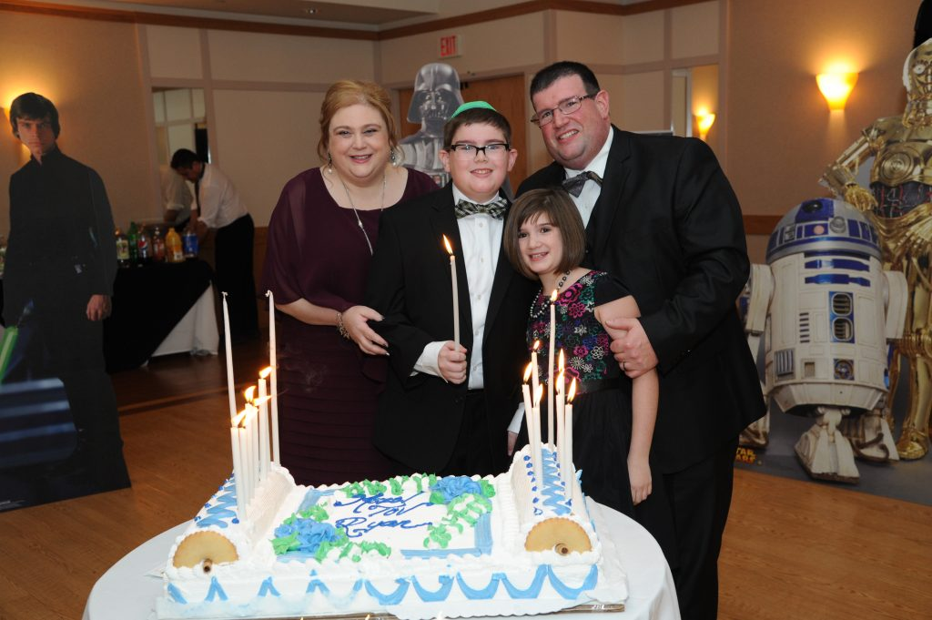 mother, father, daughter and son at the son's bar mitzvah standing in front of a cake