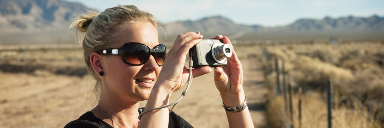 Woman taking pictures in rural field