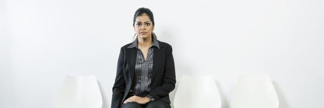 Anxious Indian woman waiting for a job interview while sitting on a row of chairs