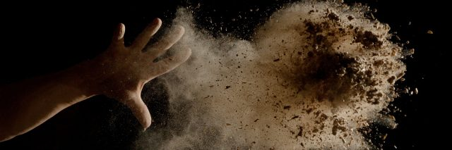 A hand throwing dirt in the air.