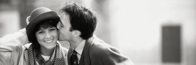 Man kissing woman on cheek, outdoors