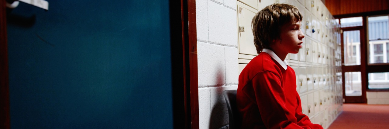 A boy sitting outside of a classroom