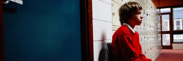 A boy sitting outside of a classroom