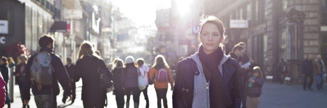 woman walking outside on a busy city street