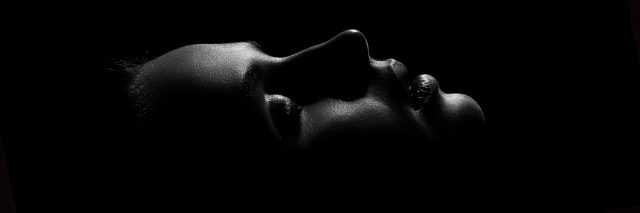 black and white portrait of a woman lying down with her eyes closed in the dark