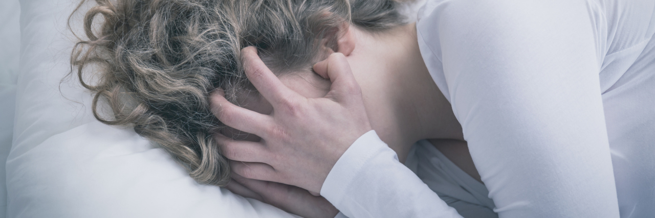 close up of young woman crying in despair covering face
