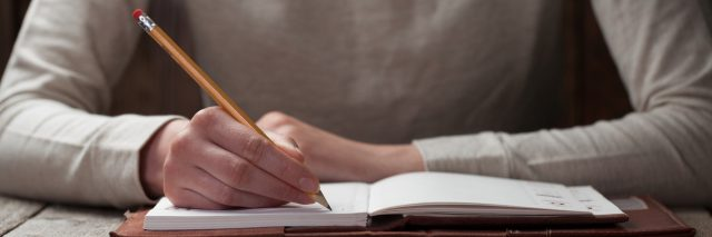A woman writing with a pencil in a journal.