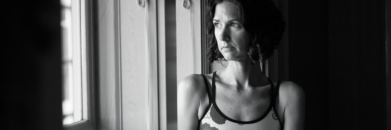 black and white photo of middle aged woman sitting on windowsill looking out