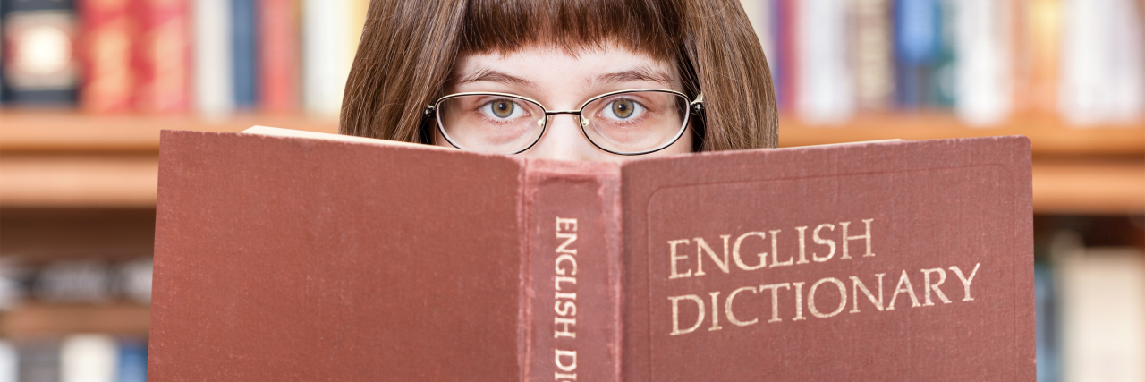 Woman looks over English dictionary.