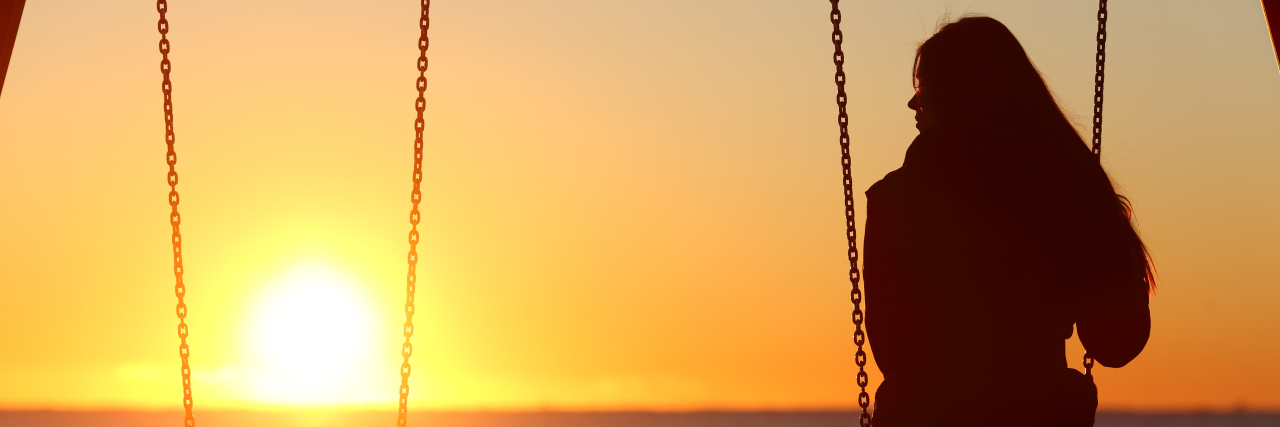 Woman on a swing at the beach at sunset,