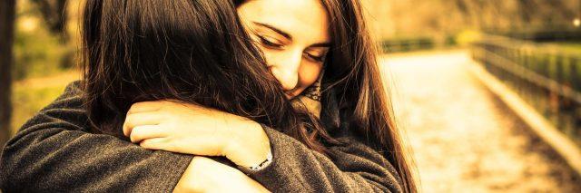 two women hugging in park in s