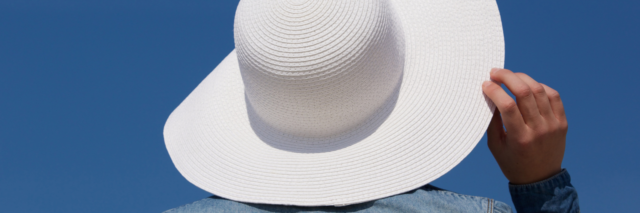 Close up portrait of the back of a young woman with white sun hat from behind
