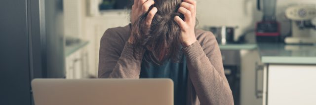 upset young woman in front of laptop pulling hair