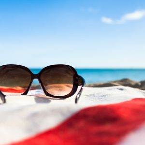sunglasses sitting on a red and white striped towel on the beach