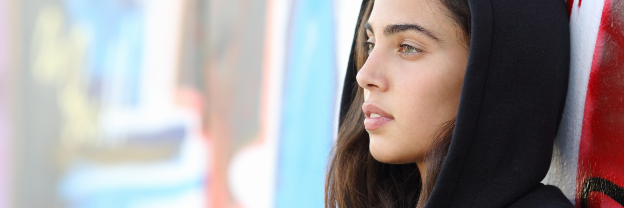 Profile portrait of a skater style teenager girl with an unfocused graffiti wall in the background
