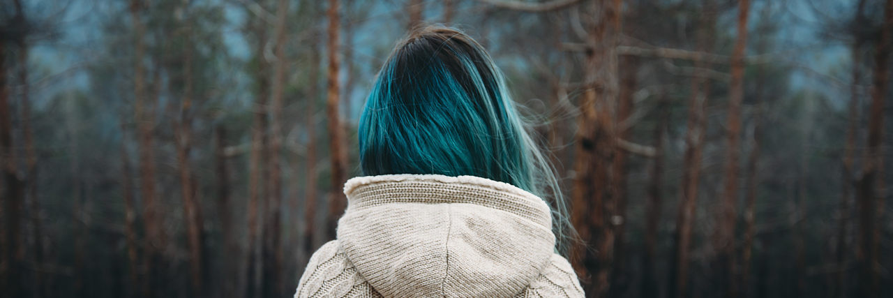 woman with blue hair wearing a white sweater and standing in front of a pine forest