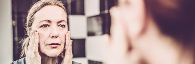 A woman touching her face and looking in the mirror at her reflection.
