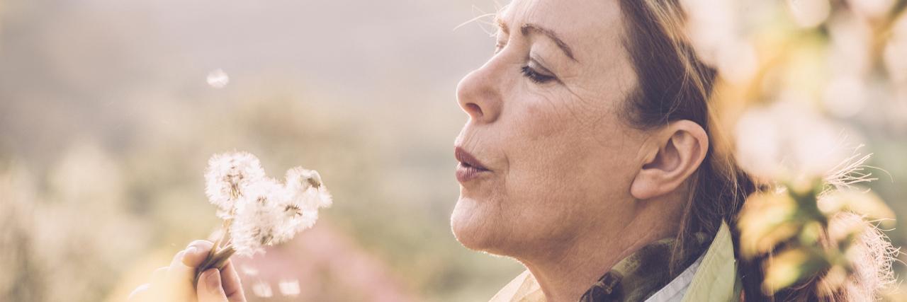 woman sitting outside blowing a dandelion