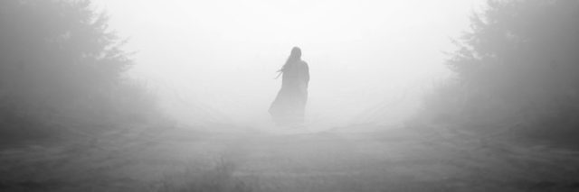 A photo of a person standing in the midst of fog.