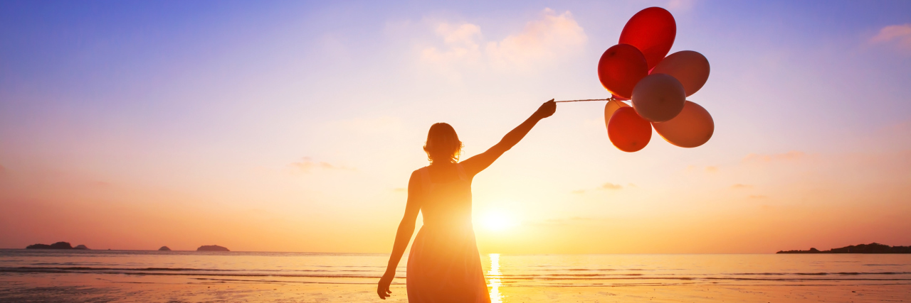 A woman walking during a sunset, holding balloons.